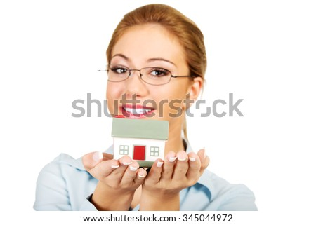 Happy businesswoman presenting a house model.