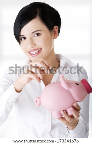 Happy businesswoman putting an euro coin into a piggy bank - stock photo