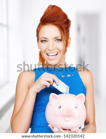 happy businesswoman putting cash money into piggy bank - stock photo