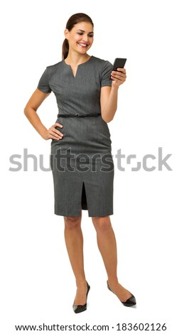 Happy businesswoman reading text message on smart phone against white background. Vertical shot. - stock photo