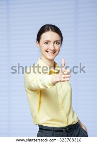 Happy businesswoman showing a thumb up sign, blue background - stock photo