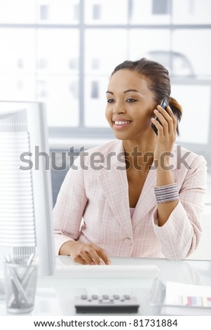 Happy businesswoman sitting at desk, looking at screen, on mobile phone call.? - stock photo