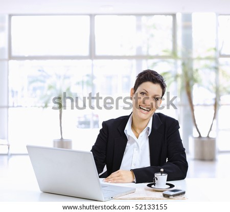 Happy businesswoman sitting at table in office lobby, using laptop computer, looking at camera laughing. - stock photo