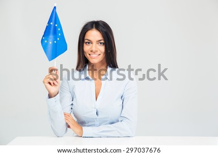 Happy businesswoman sitting at the table with european flag isolated on a white background. Looking at camera - stock photo