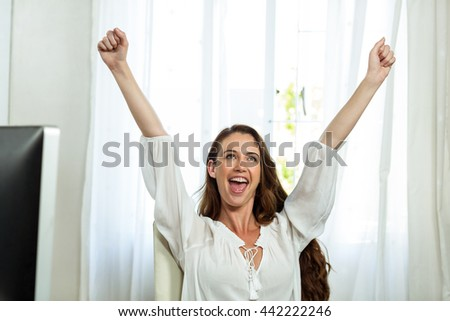 Happy businesswoman sitting on chair with arms raised in office