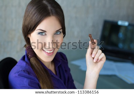 Happy businesswoman smiling with sweets - stock photo