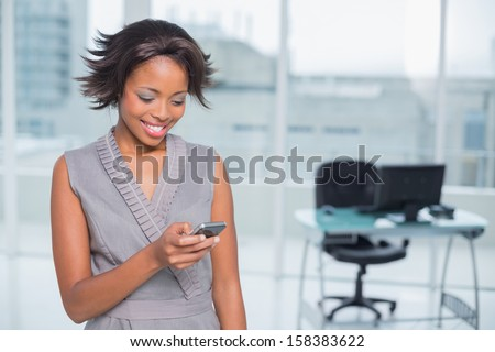 Happy businesswoman standing in her office and using phone - stock photo
