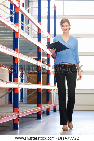 Happy businesswoman standing in next to shelves in warehouse with clipboard - stock photo