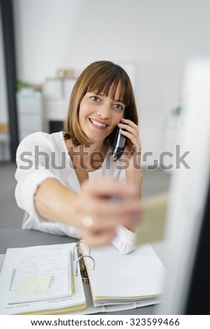Happy Businesswoman Talking to Someone on her Phone While Putting a Sticky Note for Reminders on the Side of her Computer Monitor. - stock photo