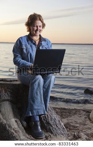 Happy businesswoman teleworking (beach) - stock photo