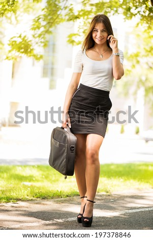 Happy Businesswoman walking on the street, holding business bag and using a Cell Phone.