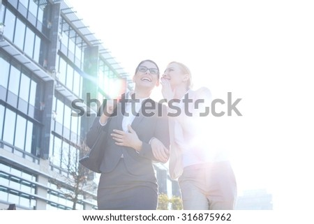 Happy businesswoman whispering in colleague's ear outside office building on sunny day - stock photo