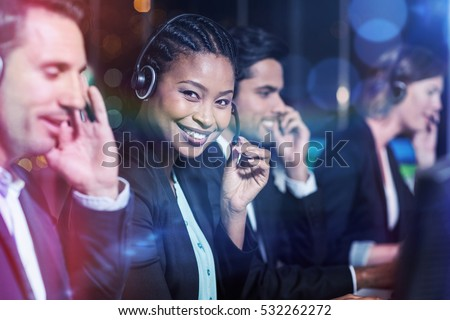 Happy businesswoman with headsets sitting by colleagues at office