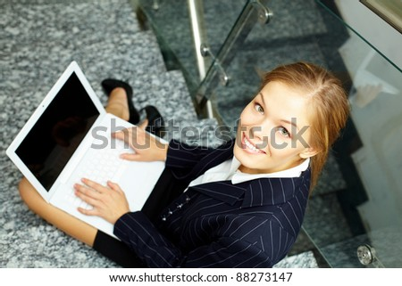 Happy businesswoman with laptop looking at camera while working on staircase - stock photo