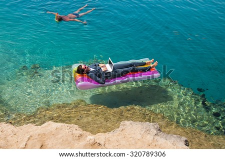 Happy businesswoman with laptop on floating mattress in red sea   - stock photo
