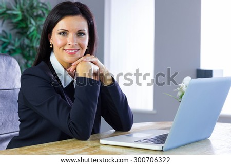 Happy businesswoman working at her desk in her office
