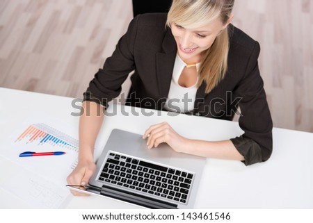 Happy businesswoman working using laptop in the office