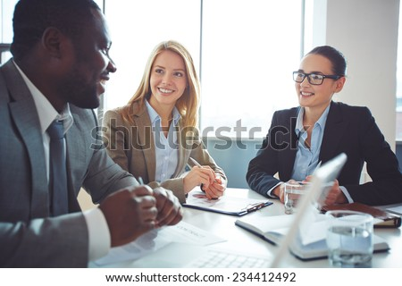 Happy businesswomen listening to young man explanations - stock photo