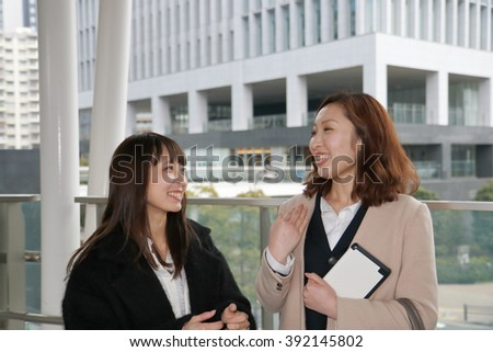 Happy businesswomen with tablet PC conversing outside office building