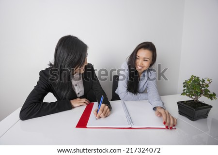 Happy businesswomen working at desk in office - stock photo