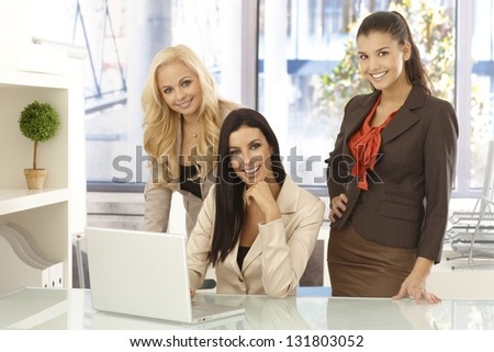 Happy businesswomen working together on computer at desk looking at camera, smiling.