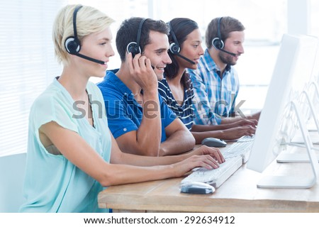 Happy call centre workers on their laptops - stock photo