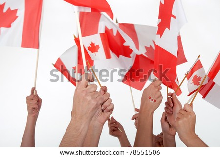Happy Canada Day! Raised hands waving Canadian flags. - stock photo