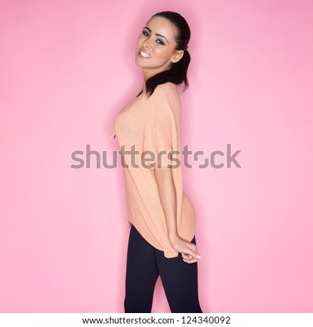 Happy carefree beautiful woman with a busty figure in trendy casual clothes smiling happily at the camera on a pink studio background - stock photo