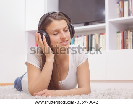 Happy Carefree Beautiful Young Woman, enjoyment in music on headphones at home - stock photo