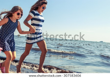 Happy carefree family running on beach at sea coast. Little girl kid with mother having fun. Summer holidays vacation. Happiness. - stock photo