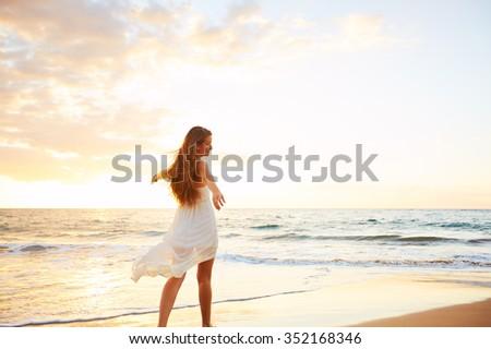 Happy Carefree Woman Enjoying Beautiful Sunset on the Beach - stock photo