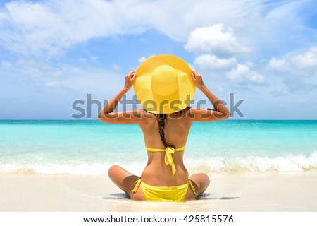 Happy carefree woman relaxing sitting in sand enjoying tropical beach destination. Perfect paradise summer vacation happiness. Back view of bikini girl holding yellow fashion hat on Caribbean holiday. - stock photo