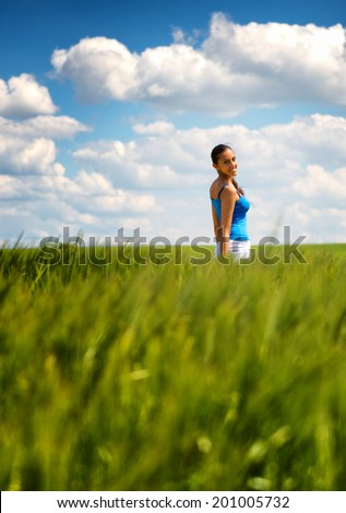 Happy carefree young woman in a green wheat field smiling as she trails her hand through the young plants, low angle distance view with copyspace against a beautiful blue sky with fluffy white clouds - stock photo