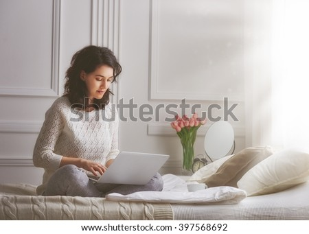 Happy casual beautiful woman working on a laptop sitting on the bed in the house. - stock photo