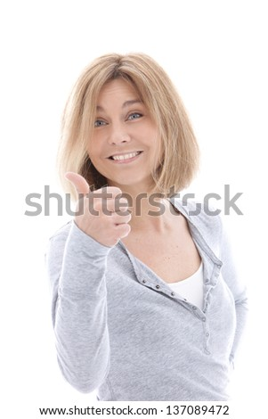 Happy casual blonde woman giving a thumbs up gesture of approval and success as she smiles at the viewer, upper body portrait isolated on white