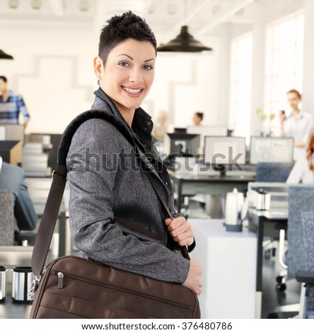 Happy casual caucasian businesswoman arriving to office with shoulder bag. Standing, looking at camera, smiling. - stock photo