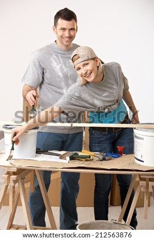 Happy casual, caucasian couple busy renovating painting new home. - stock photo