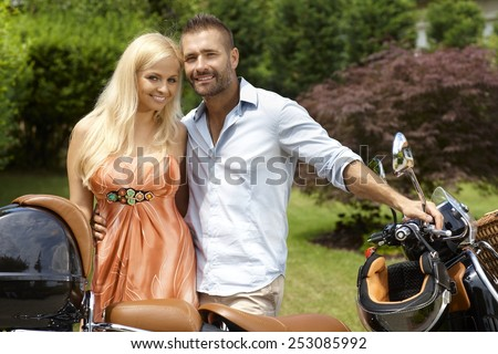 Happy casual caucasian couple with scooter in outdoor garden. Handsome man, blonde attractive smiling woman, looking at camera. - stock photo