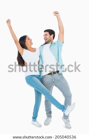 Happy casual couple cheering together on white background