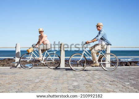 Happy casual couple going for a bike ride on the pier on a sunny day - stock photo