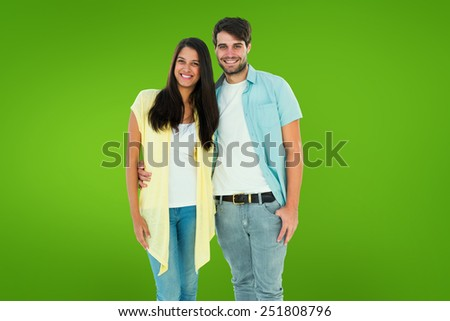 Happy casual couple smiling at camera against green vignette - stock photo
