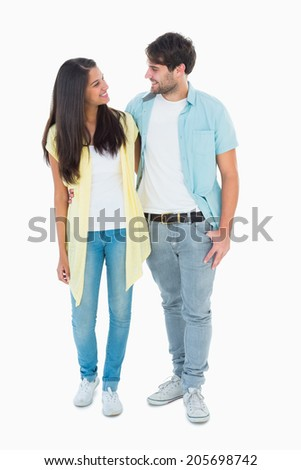 Happy casual couple smiling at each other on white background