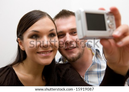 happy casual couple together taking picture - stock photo