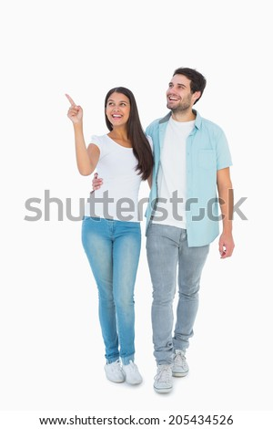 Happy casual couple walking together on white background - stock photo