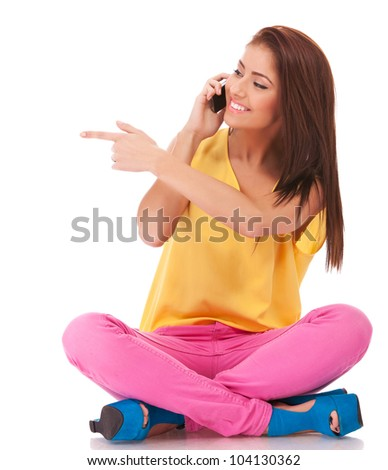 happy casual female talking on cell phone and gesturing with pointed finger to her right side - stock photo