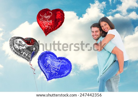 Happy casual man giving pretty girlfriend piggy back against cloudy sky - stock photo