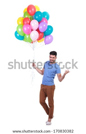 happy casual man holding a bunch of balloons is inviting to a party - stock photo