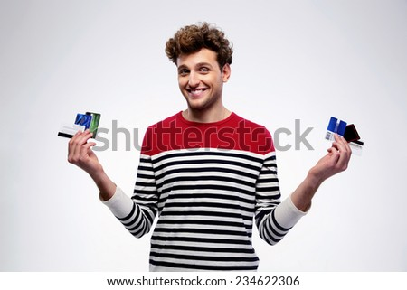 Happy casual man holding credit cards over gray background - stock photo