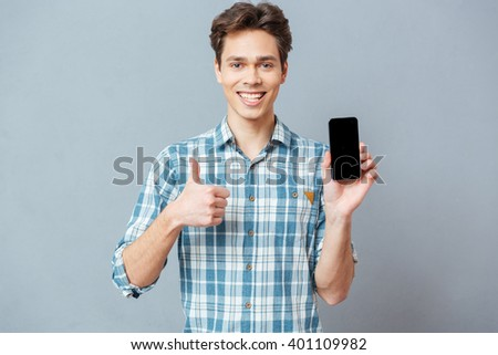 Happy casual man showing blank smartphone screen and thumb up over gray background