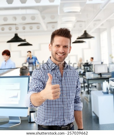 Happy casual man showing thumb-up in office, smiling. - stock photo